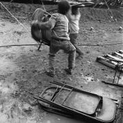 Circo Magnum / Dos niños cargan sillas un día de lluvia, en Brazo Oriental, Montevideo, el 30 de agosto de 1995.